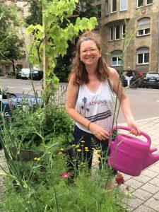Eine lachende Frau mit Gießkanne steht bei zwei Pflanzfässern mit Weinreben und Gartenblumen.
